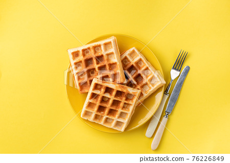 Belgian waffles on plate on yellow background 76226849