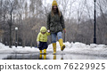Mom and daughter walking in a puddle in yellow rubber boots 76229925