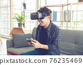Happy young man with virtual reality headset or 3d glasses with controller gamepad playing video game at home. 76235469