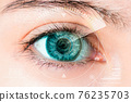 Close-up shot of young woman wearing or remove contact lens. 76235703