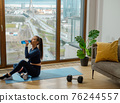 Sportive lady with ponytail in tracksuit drinks water on mat 76244557