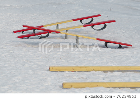 Baby seesaws outside on playground with crumbly melting spring snow 76254953