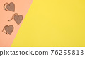 Yellow-cream background with three hearts and free space to insert text. 76255813