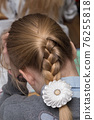 A short pigtail on the back of the girl's head with a bow. 76255818