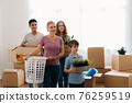 Young family unpacking things in new house 76259519