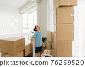 Boy looking at pile of cardboard boxes 76259520