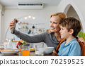 Mother taking selfie with son during breakfast 76259525