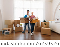 Couple holding cardboard box at home 76259526