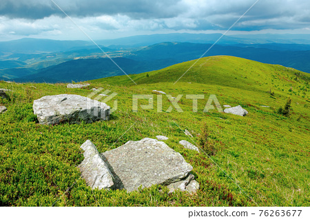 rock among the grass on the mountain meadow. beautiful green nature scenery in summer. view in to the distant valley. clouds above the highland ridge 76263677