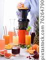 A woman prepares citrus juices on a juicer. 76264790