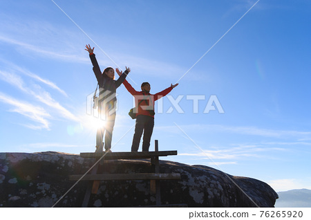 Father and daughter open arms enjoying the view of landscape after climb mountain peak 76265920