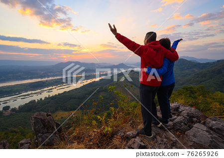 Senior healthy couple hiked the hill to see the sunrise view over Mekong river at Phu Pha Dak hill in Nong Khai, Thailand 76265926