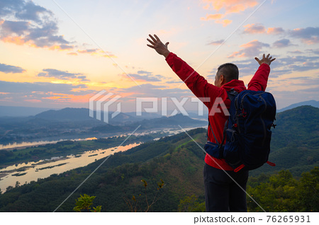 Senior man standing the cliff open arms enjoying the view of Mekong river at sunrise at phu pha dak in nong khai, Thailand 76265931