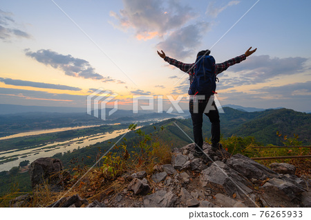 Rear view of man open arms standing on the cliff enjoying watch Mekong river at sunrise 76265933