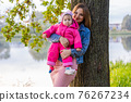 Young mother with her daughter on a warm autumn evening. 76267234