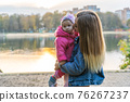 Young mother with her daughter on a warm autumn evening. 76267237
