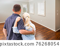 Young Couple Facing Empty Room of New House 76268054