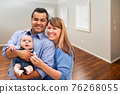 Young Couple With Baby In Empty Room of New House 76268055