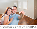 Young Military Couple Showing Off House Keys in Empty Room of New Home 76268056