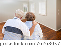 Senior Couple Facing Empty Room of New House 76268057