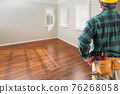 Contractor Wearing Toolbelt and Hard Hat Facing Empty Room with Hard Wood Floors 76268058