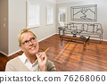 Woman With Pencil In Empty Room of New House with Couch and Table Drawing on Wall 76268060