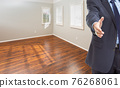 Real Estate Agent Reaches for Handshake Inside Empty Room of New House 76268061