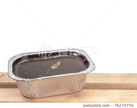 Chocolate fudge cake, a close up of homemade mousse brownie cake in aluminum foil cup isolated on white background. 76274756