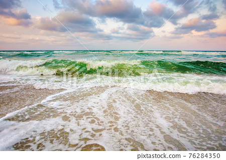 sea tide on a cloudy sunset. green waves crashing golden sandy beach. storm weather approaching. summer holiday concept 76284350