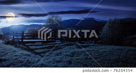 trees behind the fence on the grassy meadow at night. spring rural landscape in full moon light. distant mountain ridge beneath a bright sky with fluffy clouds 76284354