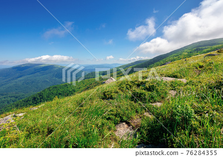 mountain meadow on a sunny morning. cloud rolling above the hill with rocks among the grass. warm summer weather. beauty of carpathian landscape in green and blue 76284355