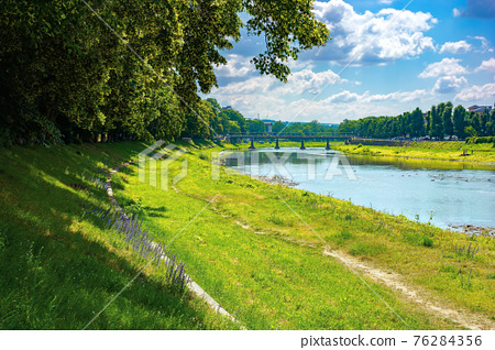 embankment of the river uzh. wonderful urban scenery in summer. view from beneath the shadow of a linden tree branches. bridge in the distance 76284356