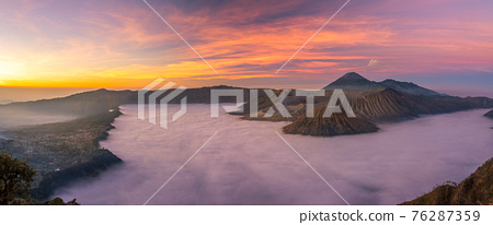 Panorama view of Mount Bromo volcano at sunrise in East Java, Indonesia surrounded by morning fog 76287359