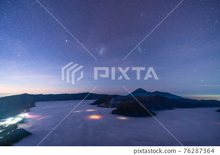 Mount Bromo volcano with million stars at night in East Java, Indonesia surround by morning fog. 76287364