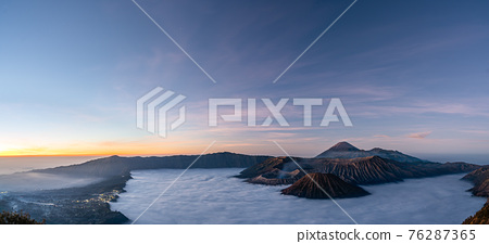Panorama view of Mount Bromo volcano at sunrise in East Java, Indonesia surrounded by morning fog 76287365