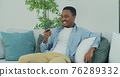 African man holding debit card and using smartphone for shopping at home. Online Payment. 76289332