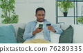 African man holding debit card and using smartphone for shopping at home. Online Payment. 76289335