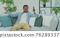 Young African American man with smartphone making video call while sitting on couch in living room. Portrait of happy man mobile video calling , sitting on sofa at home. 76289337