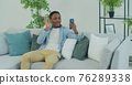 Young African American man with smartphone making video call while sitting on couch in living room. Portrait of happy man mobile video calling , sitting on sofa at home. 76289338