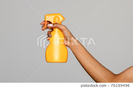 Hand of a black woman holding a yellow plastic spray bottle 76289496