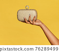 Young black woman holding a stylish gold metallic pochette 76289499