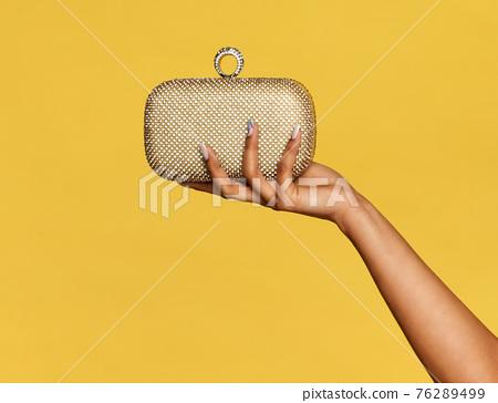 Young black woman holding a stylish gold metallic pochette 76289499