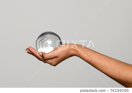 Hand of a young black woman holding a transparent glass sphere 76289500