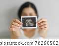 Happy Young Pregnant woman holding showing ultrasound scan photo. 76290502