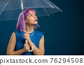 Unusual violet haired woman stands under umbrella blue in studio. Concept of fashionable girl 76294508