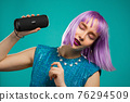Unusual woman with dyed violet hairstyle listening to music by wireless portable speaker - modern 76294509