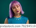 Portrait of hipster woman with dyed violet hair over turquoise studio background. Positive young 76294510