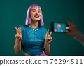 Smiling fashion blogger hipster woman making online new video blog, vlog, with her smartphone on 76294511