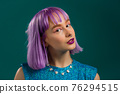 Portrait of hipster woman with dyed violet hair over turquoise studio background. Positive young 76294515