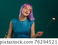 Hipster woman with sparkling bengal fire on green background. Christmas holiday concept. Young dyed 76294521